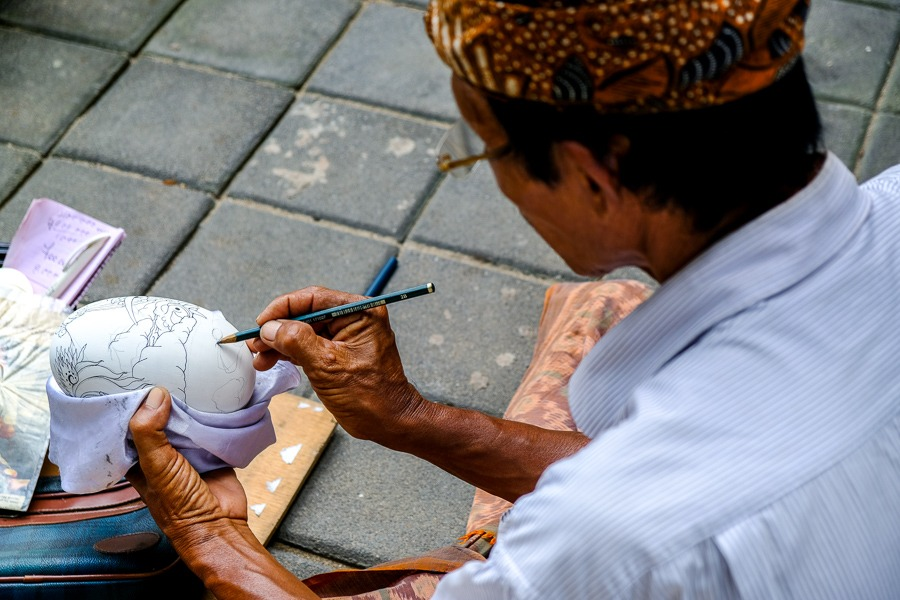 Old man painting eggs at Sanur Beach in Bali