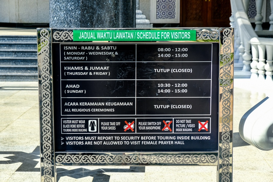 Entrance sign explaining rules and entry times at the Jame'Asr Hassanil Bolkiah mosque in Brunei