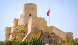 Castle keep and Omani flag at Nakhal Fort in Oman