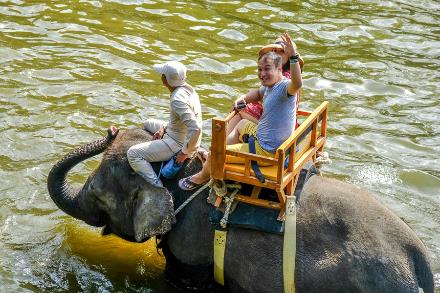 Happy tourists taking an elephant ride at the Bali Zoo