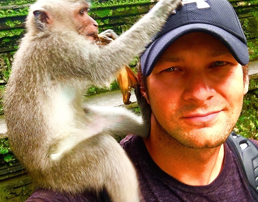 Travel guy with a monkey on his shoulder at the Ubud Monkey Forest in Bali