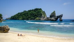 Couple relaxing with their kid on the sand at Atuh Beach in Nusa Penida, Bali