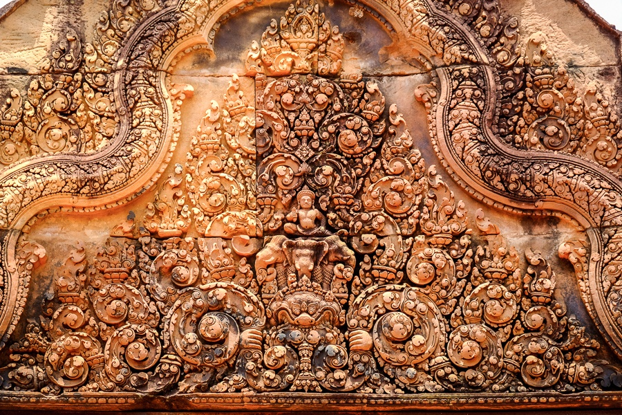 Intricate Hindu carvings in an orange stone wall