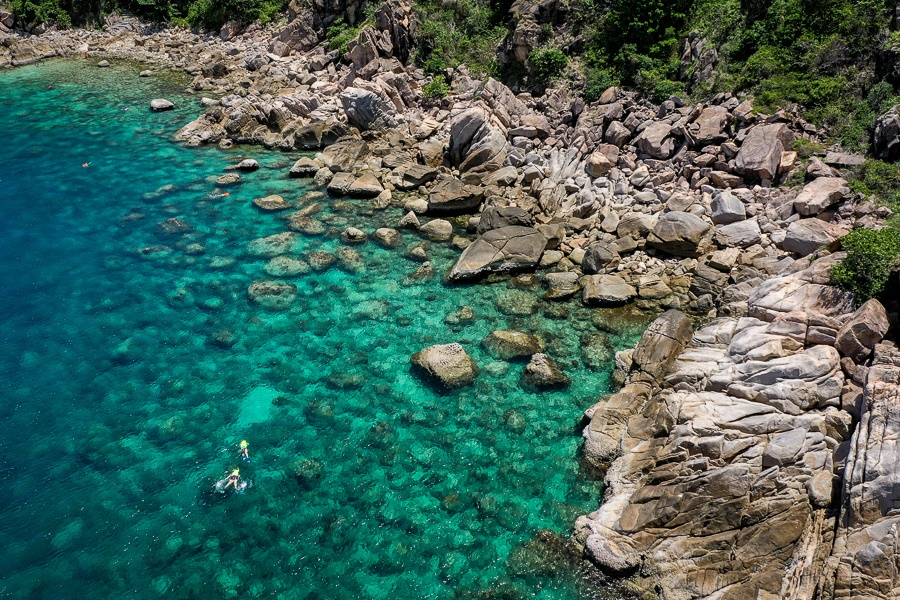 Drone view of snorkelers at coastal rocks